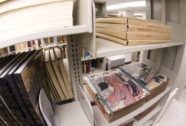 Several items stacked on shelves of Special Collections