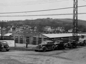 Prefabricated buildings at the first site of Triple Cities College with cars parked in front in 1946