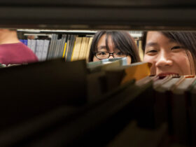 A student peeks through the shelves of the Bartle stacks