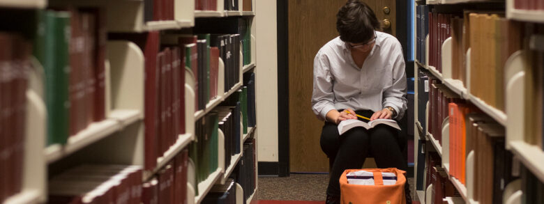 A student studies a book among the Bartle stacks