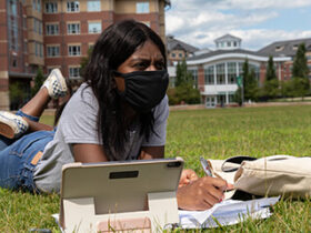 A female student lays in the grass studying while wearing a mask