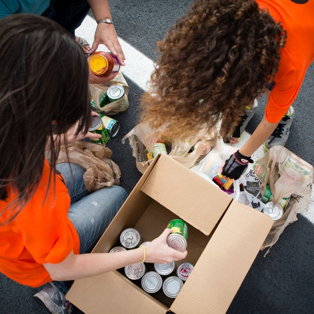 Women putting canned food into a cardboard box