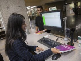 Student library worker checking out book to another student at circulation desk