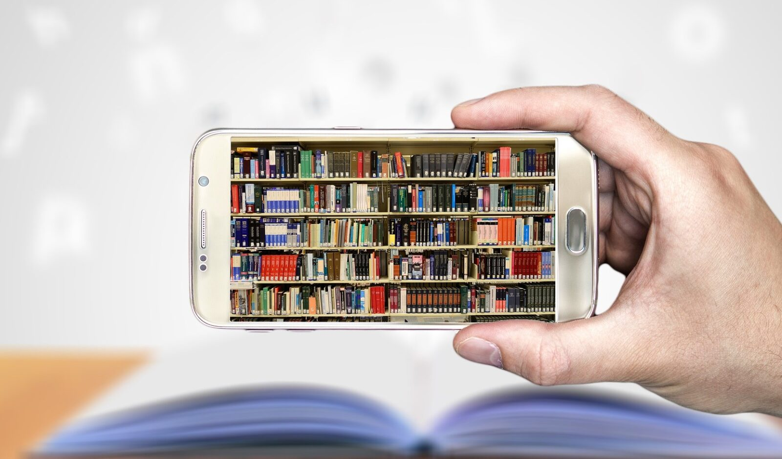 Hand holding phone with image of book shelves