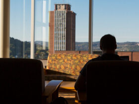 A student in silhouette studies in the foreground with the Library Tower in the background