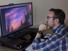 Man sitting at desk looking at image of sunset on a computer