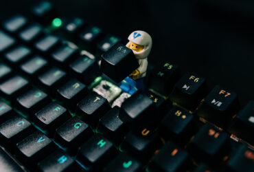 A lego minifigure is posed as if it is removing a key from a keyboard